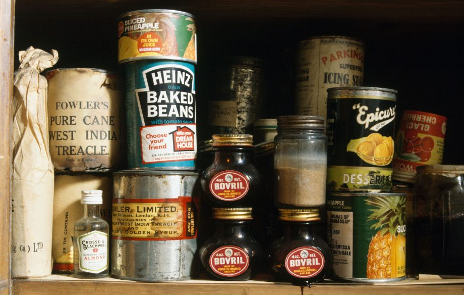 Close up of Marmite and tinned beans and fruit on wooden shelves in larder