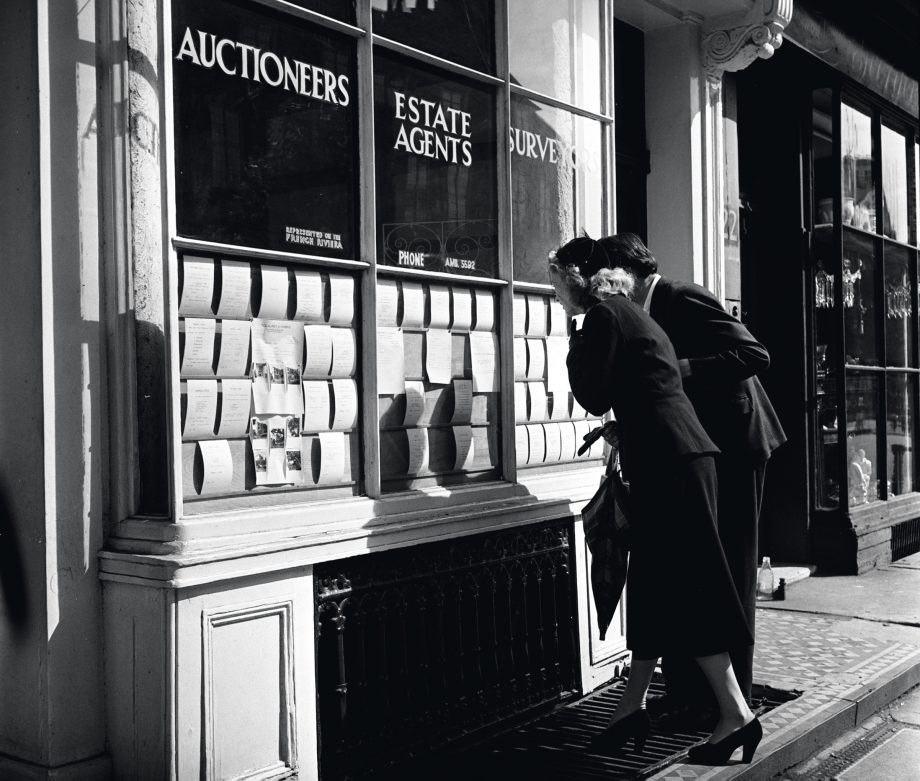England, 1950, A couple are pictured house hunting as they look at the cards on display in an Estate Agents