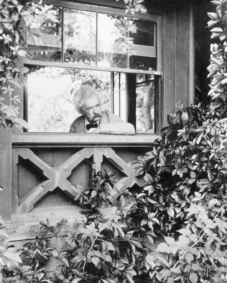Mark Twain at his writer's desk in Elmira, NY, looking out of the window.