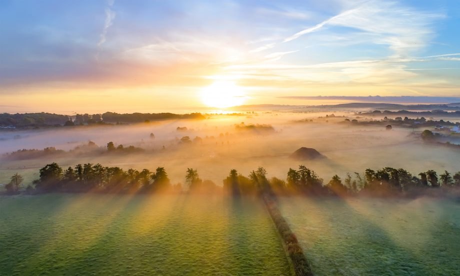Colorful sunrise on foggy day over Tipperary mountains and fields.