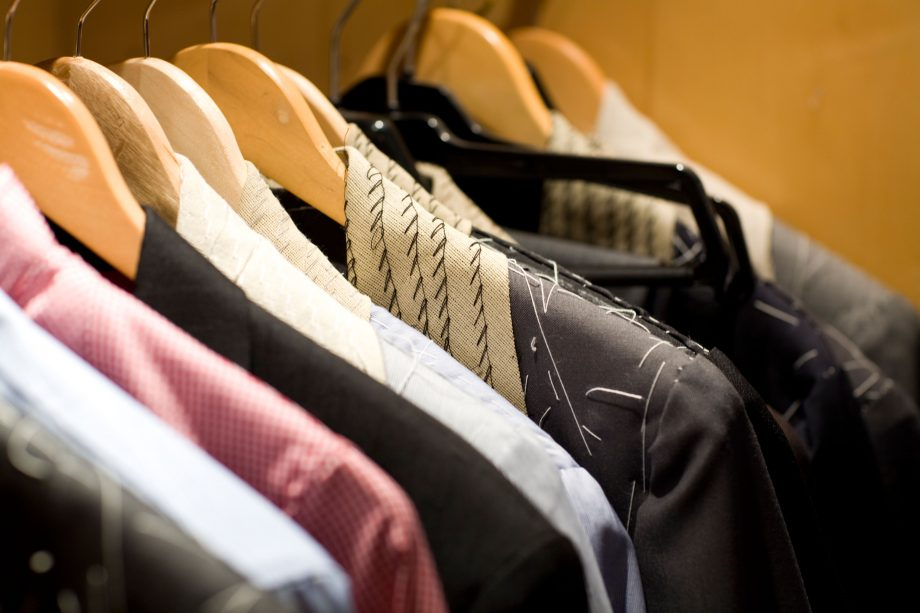 Tailored suits hang up in a tailor store.