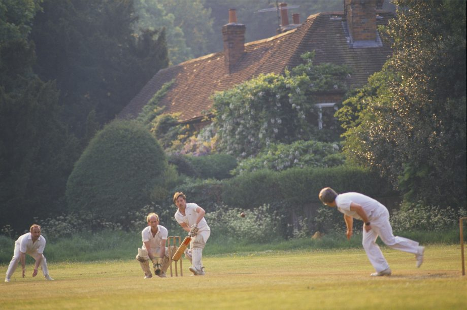 Men playing village green cricket