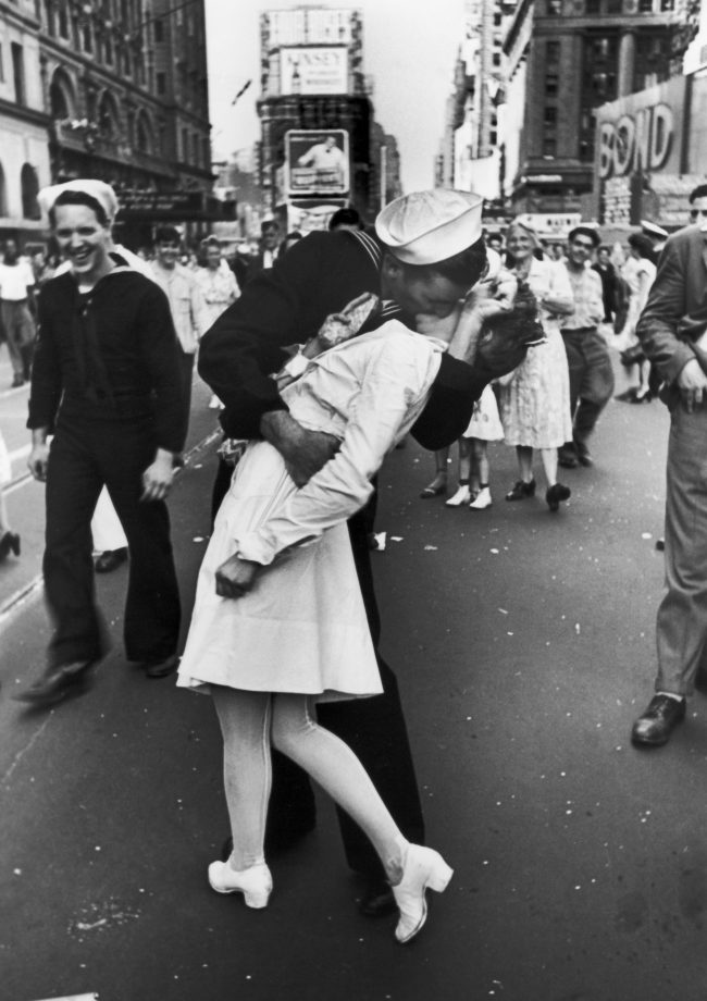 A jubilant American sailor clutching a white-uniformed nurse in a back-bending, passionate kiss as he vents his joy while thousands jam Times Square to celebrate the long awaited-victory over Japan. This photo — perhaps the most famous picture in history of a kiss — was taken by Alfred Eisenstaedt.