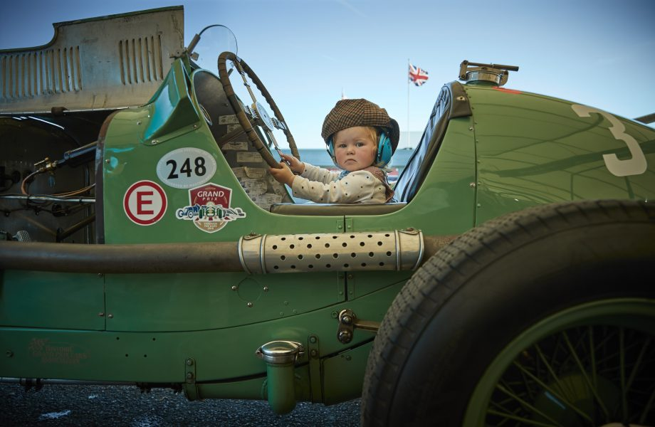 18-month-old Georgia Ricketts sits in a 1934 ERA R3A once driven by the famous racing driver Raymond Mays, which her father maintains and looks after, on day three of the Goodwood Revival Festival. Credit: Kiran Ridley/Getty Images