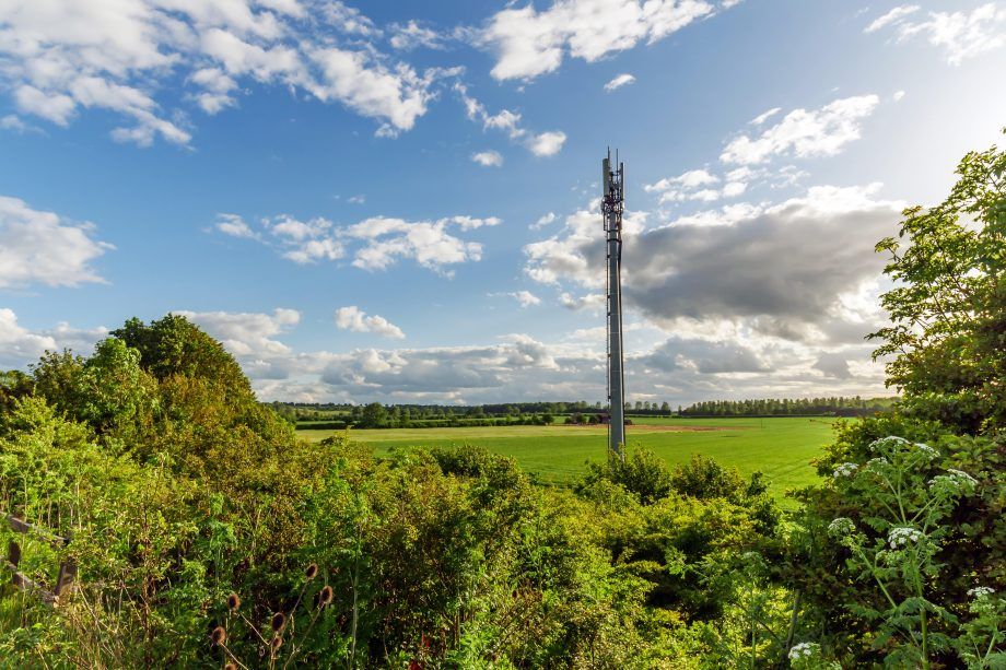 Sunset view of a British Mobile Operator Mast over field.
