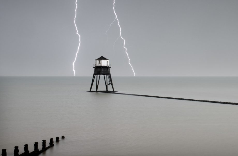 Heritage Counts 2019 – The Dovercourt Lighthouses and Causeway, Marine Parade, Dovercourt, Harwich, Essex. General view of the outer lighthouse with stormy sky and lightening, commissioned by Trinity House with work commencing in 1862 and completion in 1863. Designed with four massive tubular legs (arranged in `V'shaped pairs) to support an octagonal superstructure. The access stairs also terminate with a gate some 2m from the base, but are less elaborate than those of the inner light, reaching the doorway on the southern side in a single flight. The construction of the two storey superstructure is comparable to the inner lighthouse, with matching internal stairs, balcony, window casements and lamp aperture. A single short chimney pipe protrudes from the centre of the leaded canopy roof.