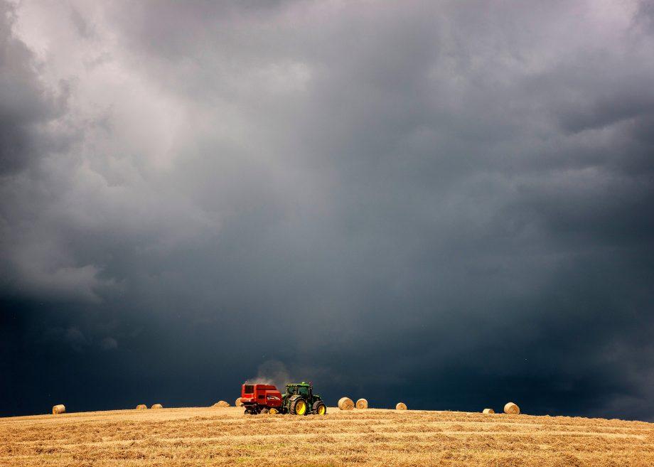 A tractor collecting hay bales under dark black stormy sky.