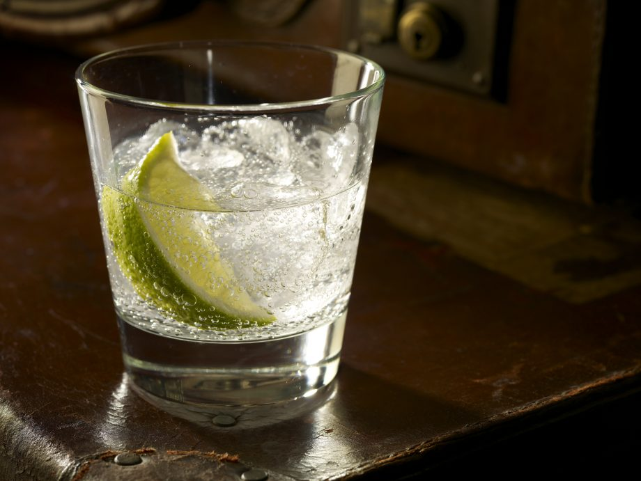 A glass of Gin and Tonic with ice and lime, sitting on old leather suitcases, because how else would you want it served?