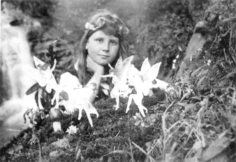 Frances Griffiths and the 'Cottingley Fairies' in a photograph made in 1917 by her cousin Elsie Wright with paper cutouts and hatpins. This photograph and others were considered genuine by a number of English spiritualists.