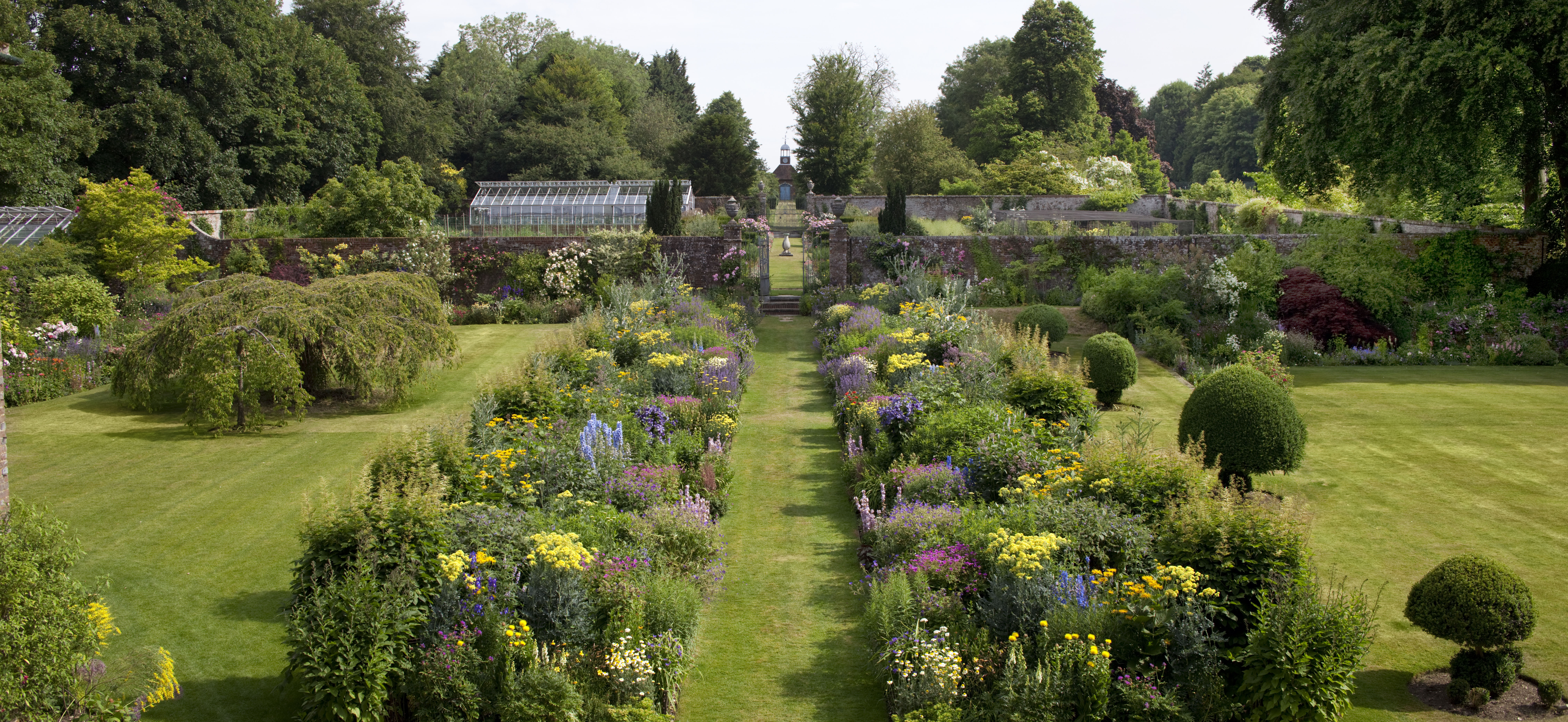 Looking down the mirrored herbaceous border in the gardens at Bramdean House.