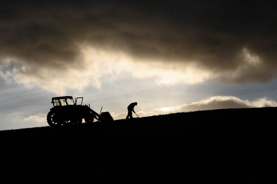 Silhouette of farmer working and tractor