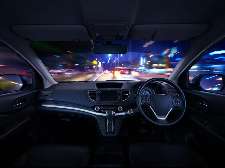 Modern black car dashboard interior with moving motion blur street background, luxury car interior concept .