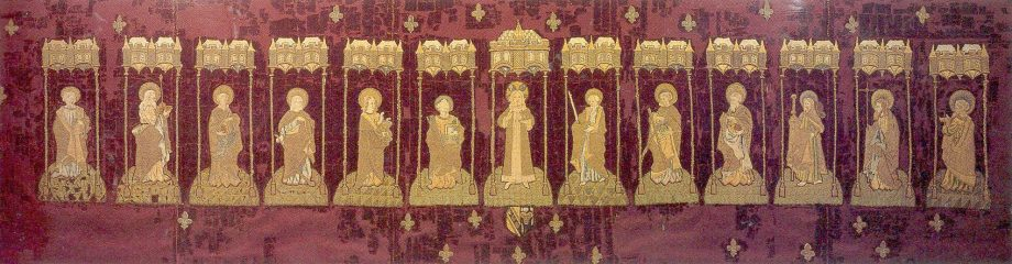 Altar frontal showing Christ and the twelve apostles, on dark crimson velvet. Bearing the arms of Sir Piers Edgcumbe and his wife Joan Durnford, who married in 1493; she died in c.1521). Each figure stands under a Gothic canopy of two oriel windows supported by thin poles. A scattering of fleur de lys over the background.