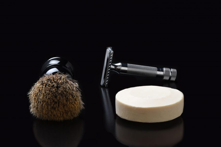 Shaving still life. A razor shaving brush and bar of soap on black.