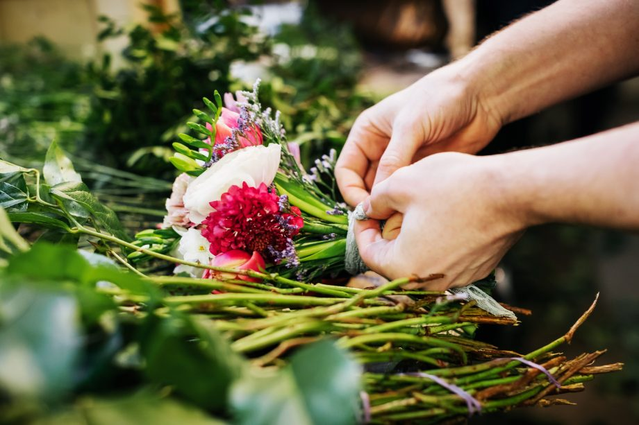 A close-up of a florist carefully preparing different flowers for a bouquet.