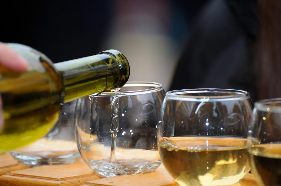 white wine poured from a bottle into a glass