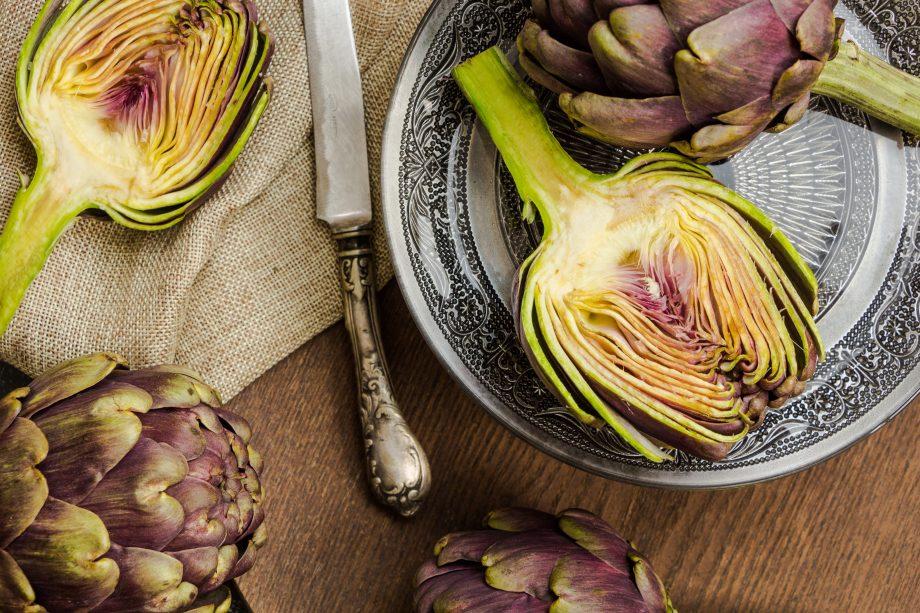 Fresh cut purple artichokes in oriental bowl closeup background