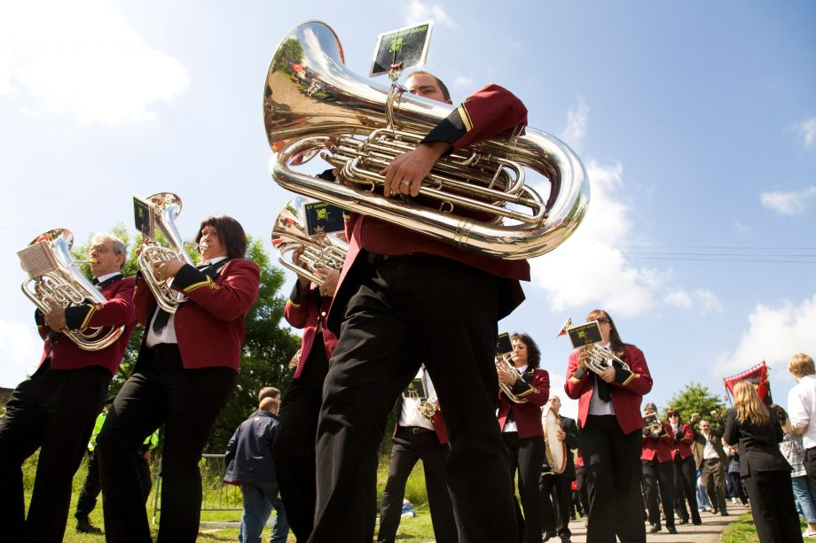A brass band marches ahead of a colliery banner