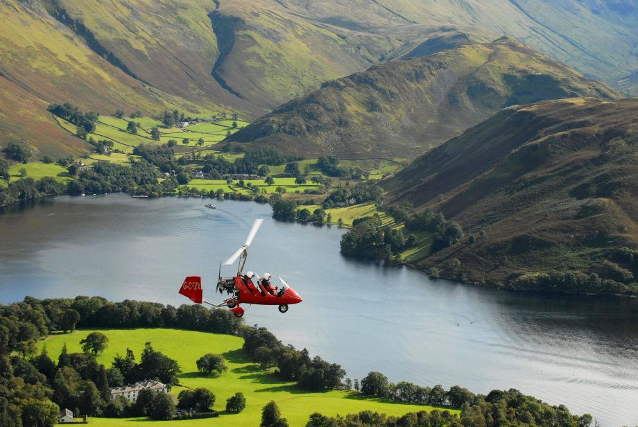 Auto gyro flying over Ullswater in the Lake District.