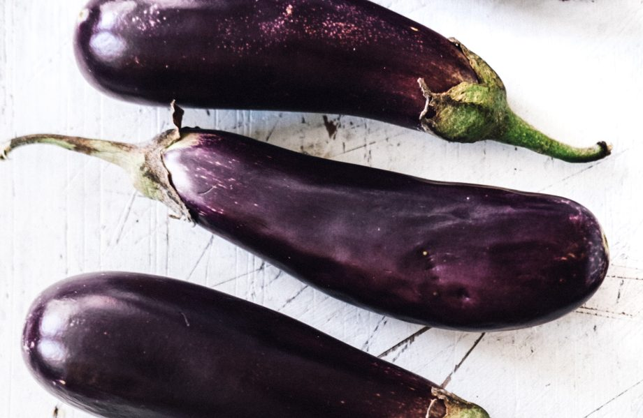 Miniature aubergines being cut and salted before cooking
